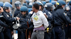 Police detain a man after a march to City Hall for Freddie Gray, Saturday, April 25, 2015 in Baltimore. Gray died from spinal injuries about a week after he was arrested and transported in a police van. (AP Photo/Alex Brandon)